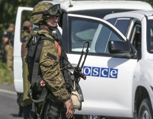 An armed pro-Russian separatist looks next to an OSCE monitoring mission in Ukraine vehicle, on the way to the site where the downed Malaysia Airlines flight MH17 crashed, outside Donetsk