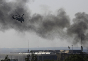A Ukrainian helicopter Mi-24 gunship fires its cannons against rebels at the main terminal building of Donetsk international airport